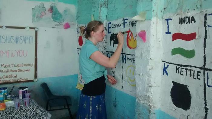 Volunteer while painting school wall